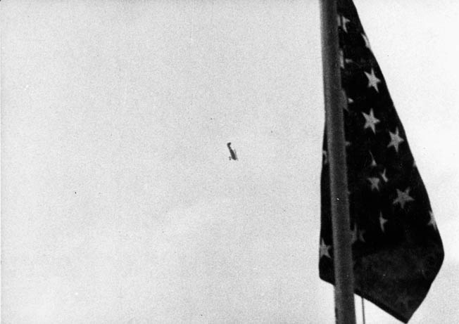 A newsreel frame shows an American flag on the Panay with a Type 96 dive bomber behind it attacking Standard Oil tankers.