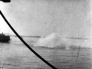 A near-miss from a Japanese bomb detonates in the water near the stranded oil tanker Miping, which was also sunk by the marauding Japanese.