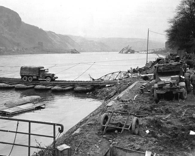 With the ruins of the collapsed Ludendorff Railroad Bridge in the background, an American truck crosses the Rhine River on a temporary pontoon bridge near the German town of Remagen.