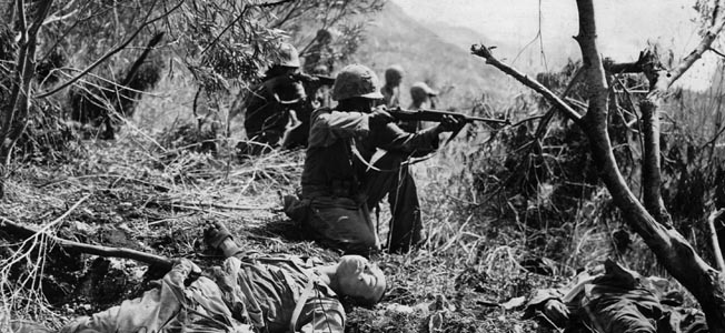 Amid the bodies of dead Japanese soldiers, a Marine of the U.S. 2nd Division raises his M1 carbine to take aim at the retiring enemy on Saipan during the advance on Mount Marpi. The bitter battle for Saipan resulted in heavy casualties for both sides.