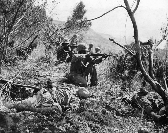 Surrounded by the bodies of slain Japanese soldiers, U.S. Marines open fire on an enemy position during their advance toward the Western beach of the island.