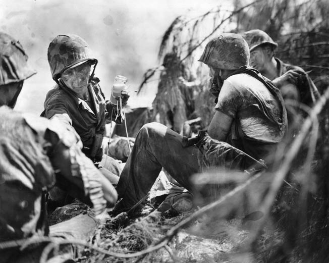 A Navy corpsman (facing camera) gives medical treatment to three wounded Marines. More than 16,000 American servicemen were casualties during the battle for the island.