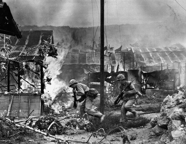 Two U.S. Marines advance through the burning ruins of Garapan, July 1, 1944. Once home to 15,000 inhabitants, the Marines found it largely deserted until the night of July 3 when 200 Japanese returned to fight.