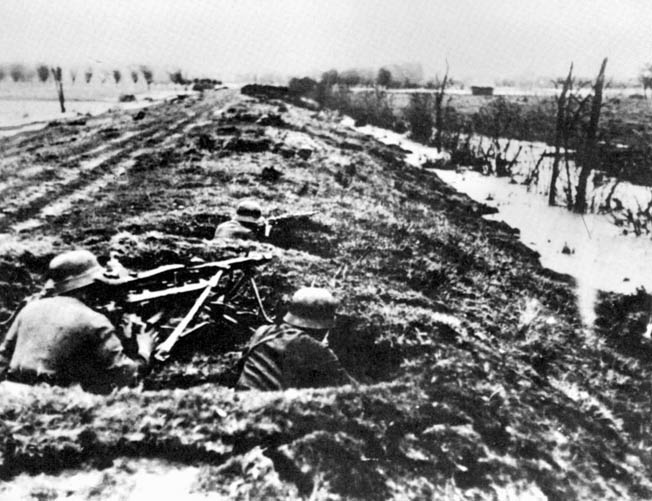 In the Breskens Pocket across the West Scheldt from Walcheren Island, German soldiers man a machine-gun position that is partially camouflaged with tree branches. The Germans put up a determined defense against Canadian troops tasked with clearing the Scheldt Estuary to open the river and the port of Antwerp to Allied supply ships.