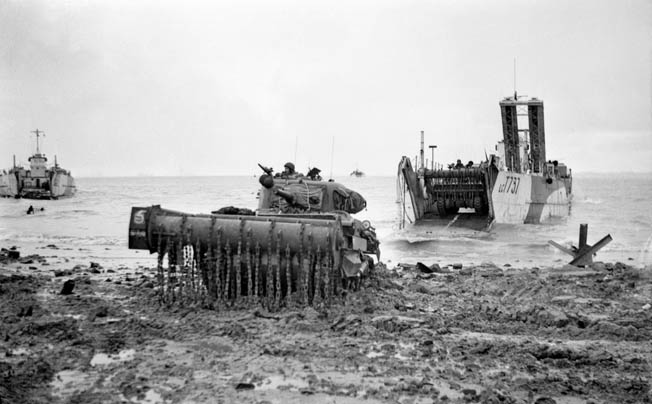 "A Sherman ""crab"" flail tank comes ashore from an LCT during the invasion of Walcheren, November 1, 1944. The drums on the front of the tank rotate, causing the chains to beat the ground and detonate land mines."