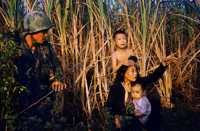 A soldier in the Korean 9th (White Horse) Division encounters a frightened Vietnamese woman and her children on patrol north of Bon Son in 1966.