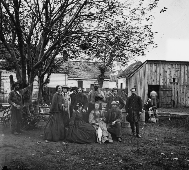 Sanitary Commission nurses and officers pose at Fredericksburg, Virginia, during the 1864 Wilderness campaign.