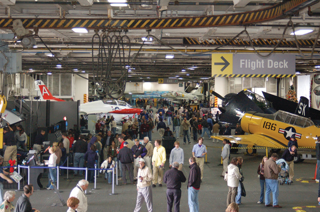 Crowds tour Midway's massive airplane hangar deck.