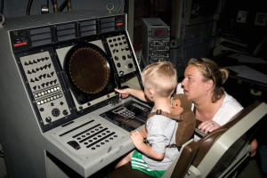 A mother and son at a cockpit flight simulator.