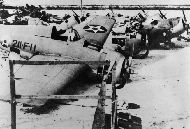 In the aftermath of Wake Island, wrecked American Wildcat fighter planes from Marine squadron VMF-211 litter the runway.
