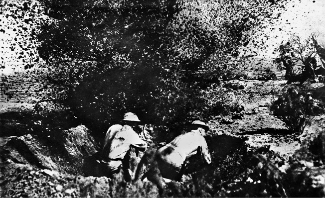 Marine defenders in a foxhole dodge an exploding shell during the first landing attempt.