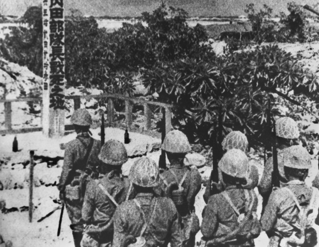 Japanese troops stand at attention to honor their fellow soldiers who were killed in the stubborn American defense of Wake Island.