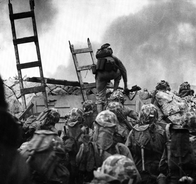 First Lieutenant Baldomero Lopez leads U.S. Marines over the seawall at Red Beach during the audacious landing at Inchon on September 15, 1950. Lopez was awarded a posthumous Medal of Honor for throwing his body on a grenade to shield his men.