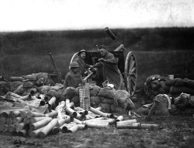 An American gun crew fires the 75mm at Saint-Michel, France, in September 1918. Note the large pile of expended shells and ammunition packing tubes behind the gun, indicating its high rate of fire. A shell casing is still in the air above the cannon.