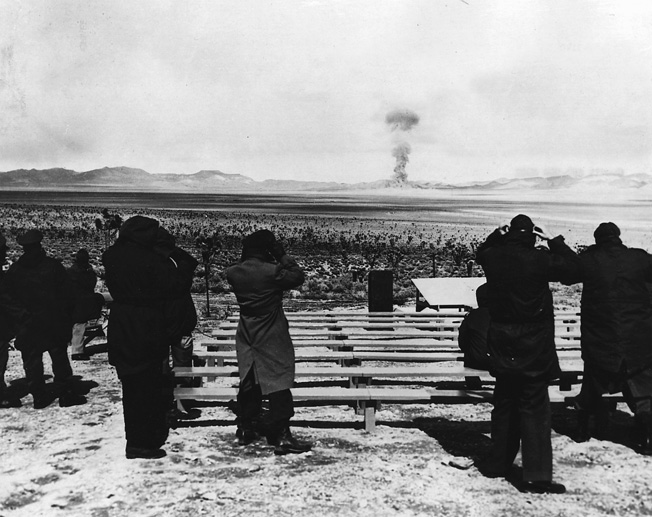 At a Nevada testing facility, the first shot of Operation Teapot is seen by official observers.