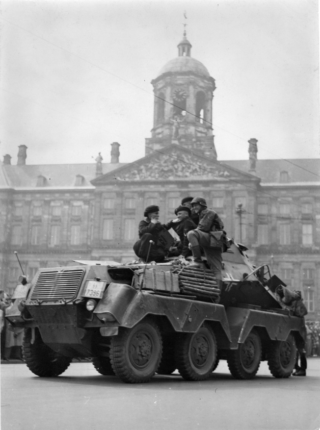 Scout troops clad in panzer uniforms and berets sit atop an SdKfz.231 (8-rad) heavy armored reconnaissance vehicle.