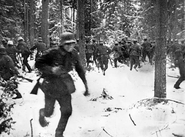 Alerted to the advance of Soviet forces nearby, Finnish troops rush to defensive positions early in the Winter War. Note the German coal scuttle-style helmets worn by the Finnish soldiers.