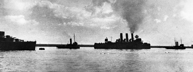 Wounded but unbowed, HMS Vindictive is towed out of Dover Harbor for her final blocking effort at Ostend.
