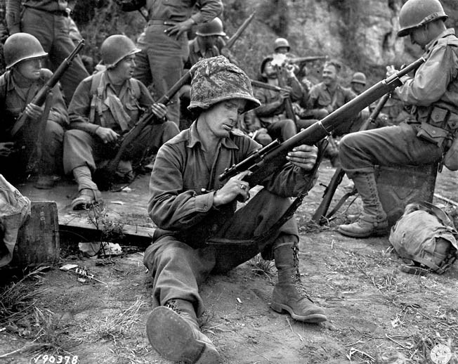 A GI with the 36th Infantry Division cleans his M1903 Springfield, equipped with sniper scope, during the Italian campaign of 1943.