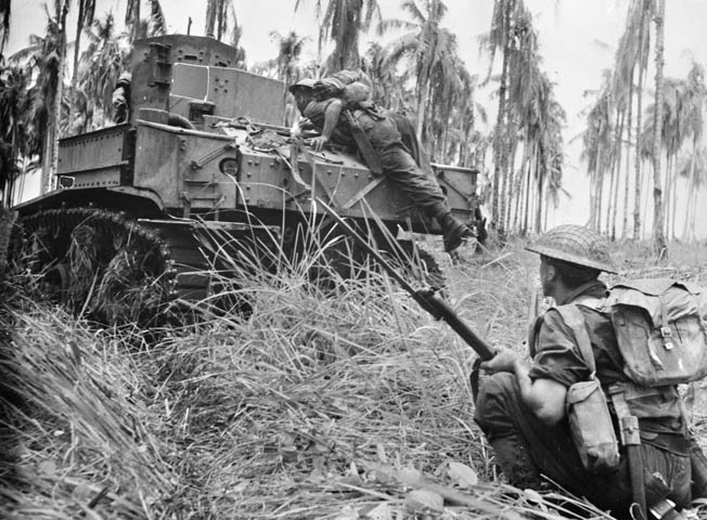 In a field of kunai grass, an Australian corporal climbs aboard a Stuart M3 light tank to warn the crew of an unseen bunker during the final attack on Buna.