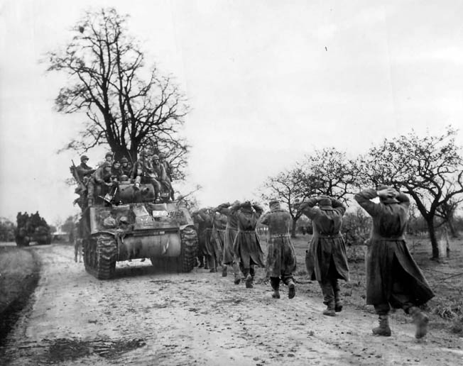 German prisoners march with their hands on their heads while American tanks and infantrymen advance toward the front following the battle around Geilenkirchen. Shortly after the fight for the Geilenkirchen salient ended, the U.S. 84th Infantry Division briefly took up defensive positions.