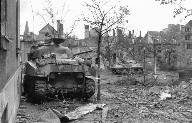 The commander of an M4 Sherman tank of the U.S. 745th Tank Battalion looks through binoculars from his turret hatch on the day before the city of Aachen fell. In the distance is an M10 tank destroyer, a lightly armored but heavily armed and open-turreted vehicle designed specifically to take on enemy tanks.