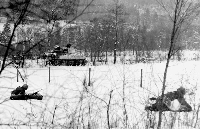 An assault tank rolls past soldiers of the 30th Infantry Division to drop 105mm artillery shells on German positions in Belgium. Miller and his battalion helped the 30th reenter La Gleize.