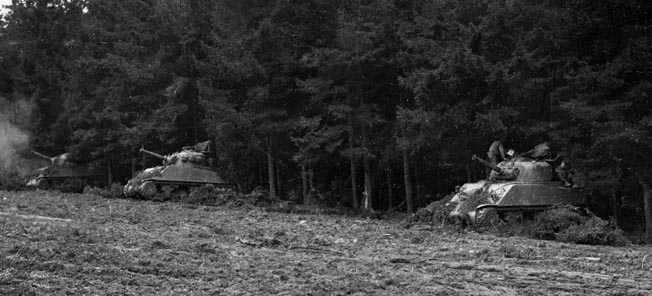 Assault tanks fire a barrage on the enemy from a tree line. Miller could often not see the targets his assault tank was firing on because of Belgium's dense woods.