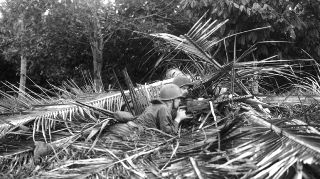 A Marine Raider machine-gun crew uses palm fronds to camouflage its position during intense training prior to the Makin Raid. The Marines fought heroically against a stout Japanese garrison on the atoll and withdrew after controversially considering surrender to the enemy.