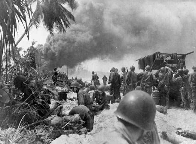 While smoke billows from stricken Japanese positions on Makin, American combat engineers lay a metal mat across the soft sand to allow tracked and wheeled vehicles to move forward without becoming mired in the terrain.