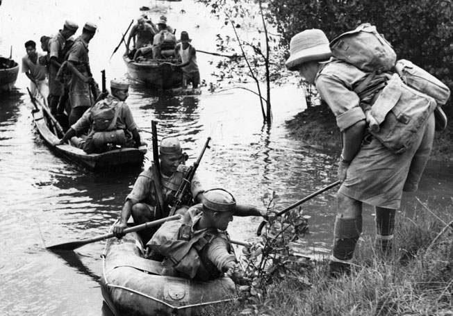 Indian soldiers cross a river during military exercises near Singapore prior to the Japanese invasion.