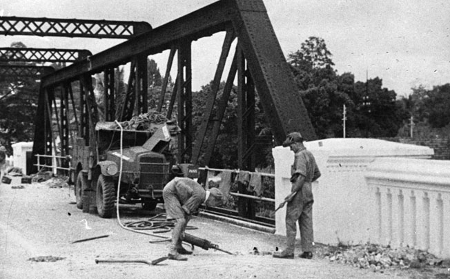 In preparation for the coming Japanese onslaught, British sappers lay explosive charges to destroy a bridge at Seremban along a probable route of enemy advance near Kuala Lumpur in late 1941.