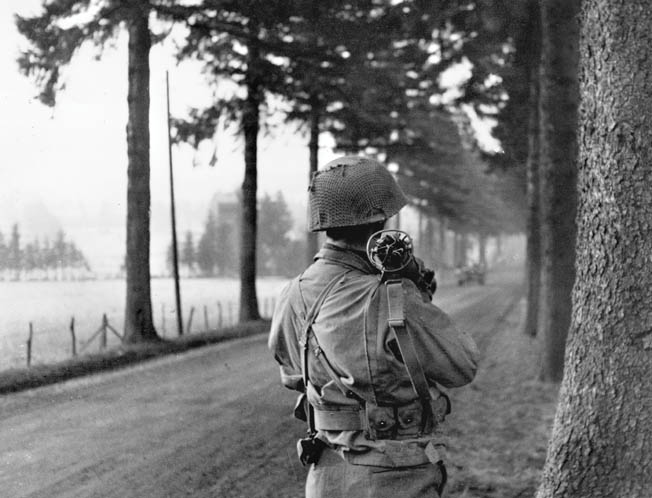 The day before the German attack on the Belgian village of Manhay, an American soldier shoulders a bazooka and stares down a tree-lined road, the likely route of approach that German tanks would utilize. The fight for Manhay occurred at the height of the Battle of the Bulge.