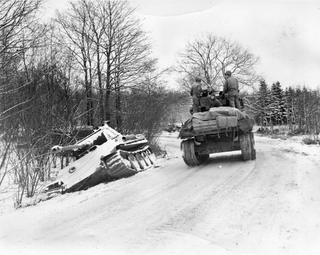 On December 27, 1944, an M4 Sherman medium tank advances toward Manhay and possible contact with German forces in the vicinity.