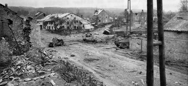 Destroyed and abandoned vehicles litter the field of combat around the Belgian town of Manhay. The town itself sustained heavy damage during the Battle of the Bulge as American troops maintained control of the area, including vital roads that led westward toward the River Meuse and the port of Antwerp.