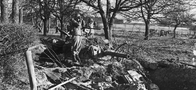 Soldiers of the 7th Armored Division stand atop a camouflaged M4 Sherman medium tank and scan the horizon for the presence of German forces near Manhay.