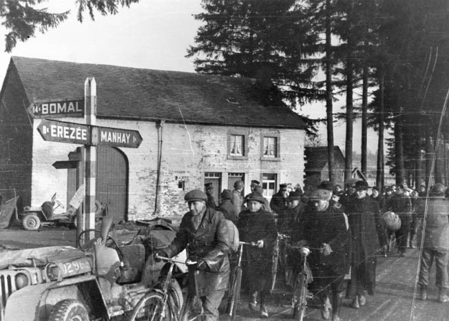 On December 23, 1944, Belgian civilians flee after being warned that a battle for the village of Manhay was looming. Many of these Belgians have bicycles ready to speed their retreat to safety.