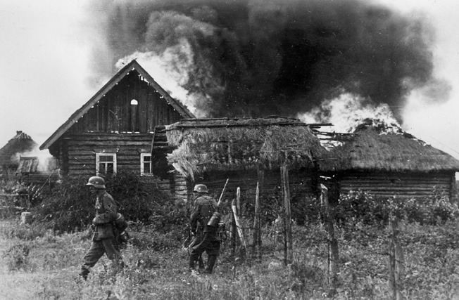 German soldiers set fire to a farm during the ruthless invasion of the Soviet Union, summer 1941. German troops and special police battalions also slaughtered Soviets in their path.