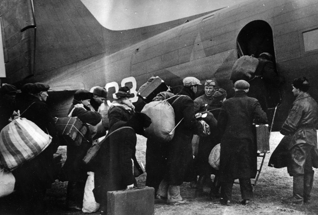 Evacuees line up to depart Leningrad in a PS-84 airplane, the Soviet version of the Douglas DC-3, October 1941.