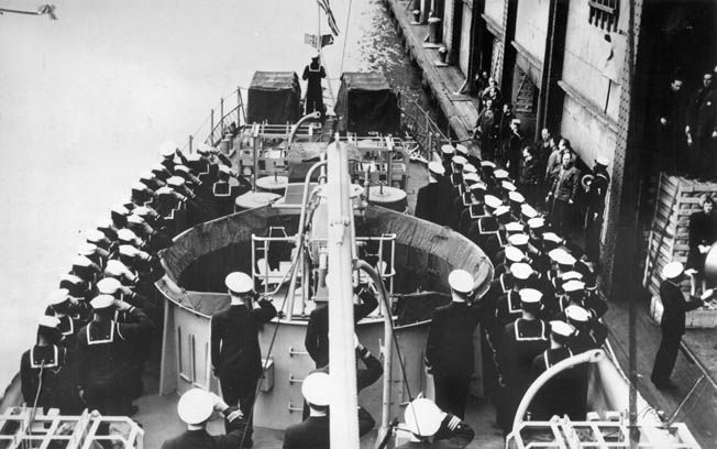 The crew of PC-1264 salutes the American flag during the ship's commissioning ceremony, April 25, 1944. The ship became the Navy's second ship to be manned by a mainly black crew.