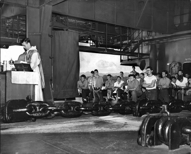 A chaplain conducts Mass aboard the carrier. Ed is to the right in the white T-shirt with arms crossed.