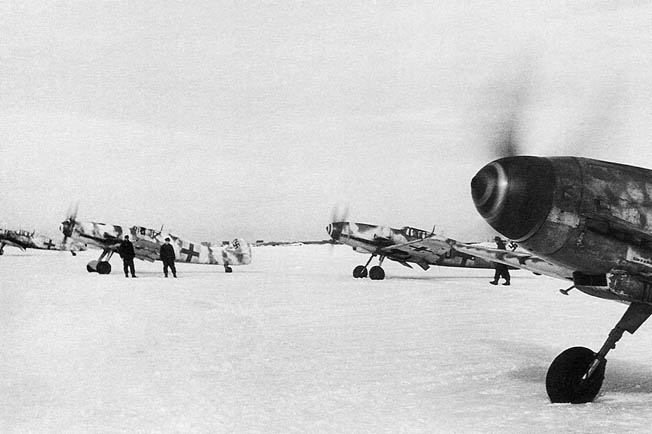 Pilots of JG 52 rev the engines of their Messerschmitt Me-109 fighter planes in preparation for takeoff from a snowbound airfield on the Eastern Front during the winter of 1943. The severe cold caused mechanical problems, while snow and ice limited fighter operations.