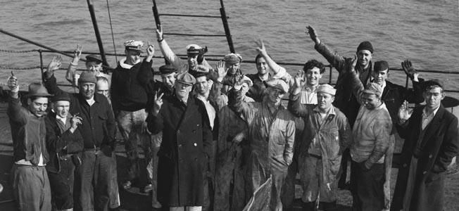 """Happy to have survived an attack by the German submarine U-123 off Cape May, New Jersey, crewmen of the tanker SS Malay give the """"V for Victory"""" gesture as they gather around damage inflicted on their ship."""