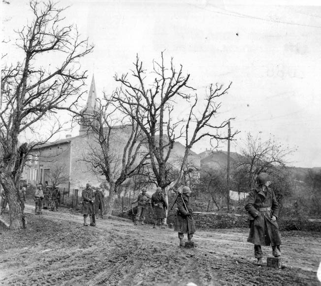 Troops of the 1st Battalion, 358th Infantry, 90th Division, halt on a road leading to Fort Koenigsmacker and look toward their formidable objective.