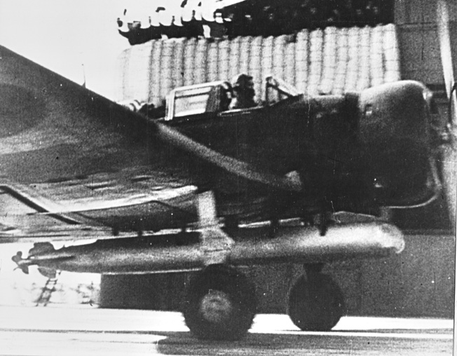 "A frame taken from a captured Japanese newsreel showing a Nakajima B5N Kate torpedo plane taking off from an unidentified aircraft carrier. The padding visible on the carrier's ""island"" behind the plane are the sailors' bedrolls."