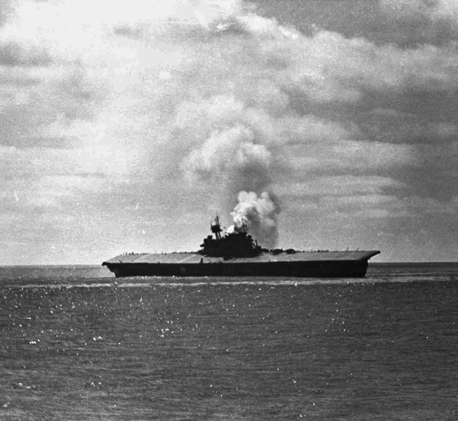 """The stricken Yorktown lists heavily as the carrier's """"island"""" burns following the second attack of the day."""