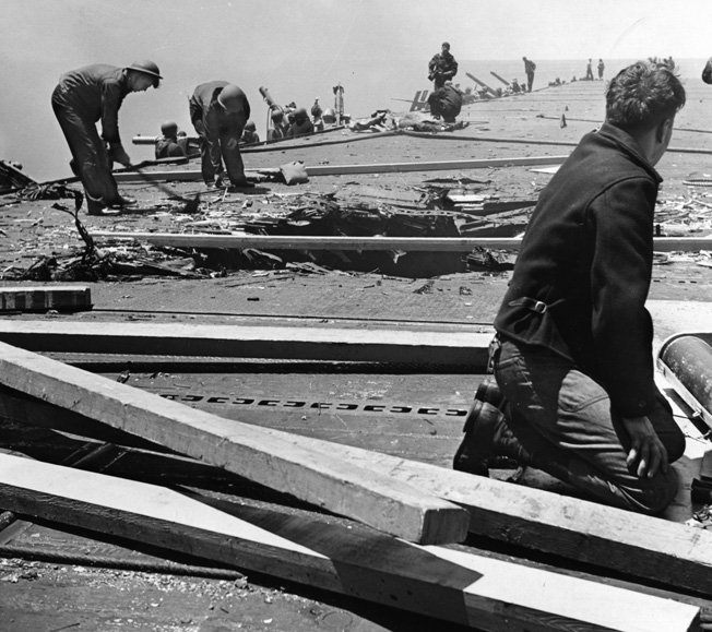 Crewmen work to repair the 12-foot hole caused by a 250 kilogram bomb that hit the flight deck. The explosion killed and wounded many men, but the flight deck was quickly repaired with timbers and steel plating, and flight-deck activities resumed.
