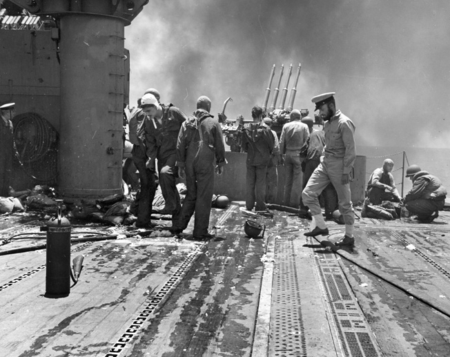 """Medical corpsmen treat casualties (right) on board Yorktown, after the carrier's flight deck had been hit by a Japanese bomb. The dead and wounded were members of the crew of 1.1"""" machine gun mount # 4 visible, in the center background."""