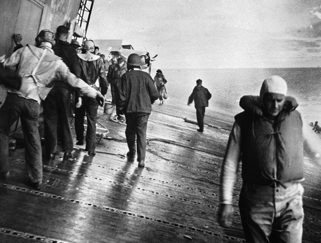 As Yorktown's list increases, sailors and air crewmen prepare to abandon ship. Ray Daves was one of those who jumped off the fantail and was later rescued.