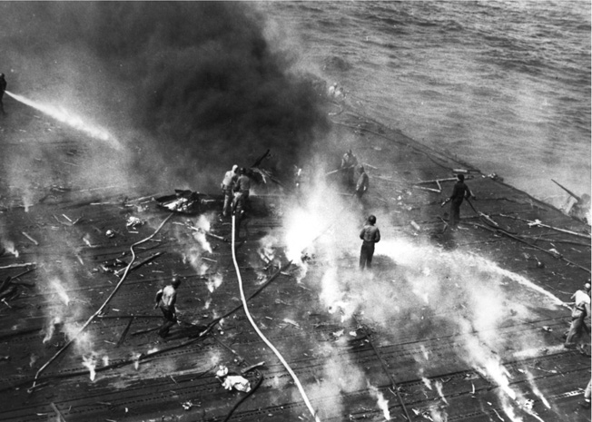 A Yorktown fire-fighting crew pours water on burning debris, mid-afternoon, June 4, after taking hits from Japanese dive bombers. Sailors quickly began repairing the damage but the ship was already crippled.